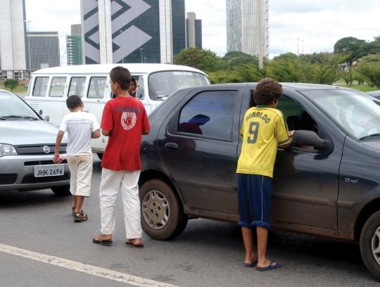 Crianças pedindo esmolas em sinaleiro