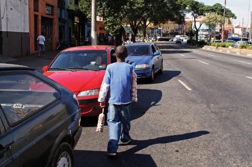 Criança vendendo alho no sinaleiro.